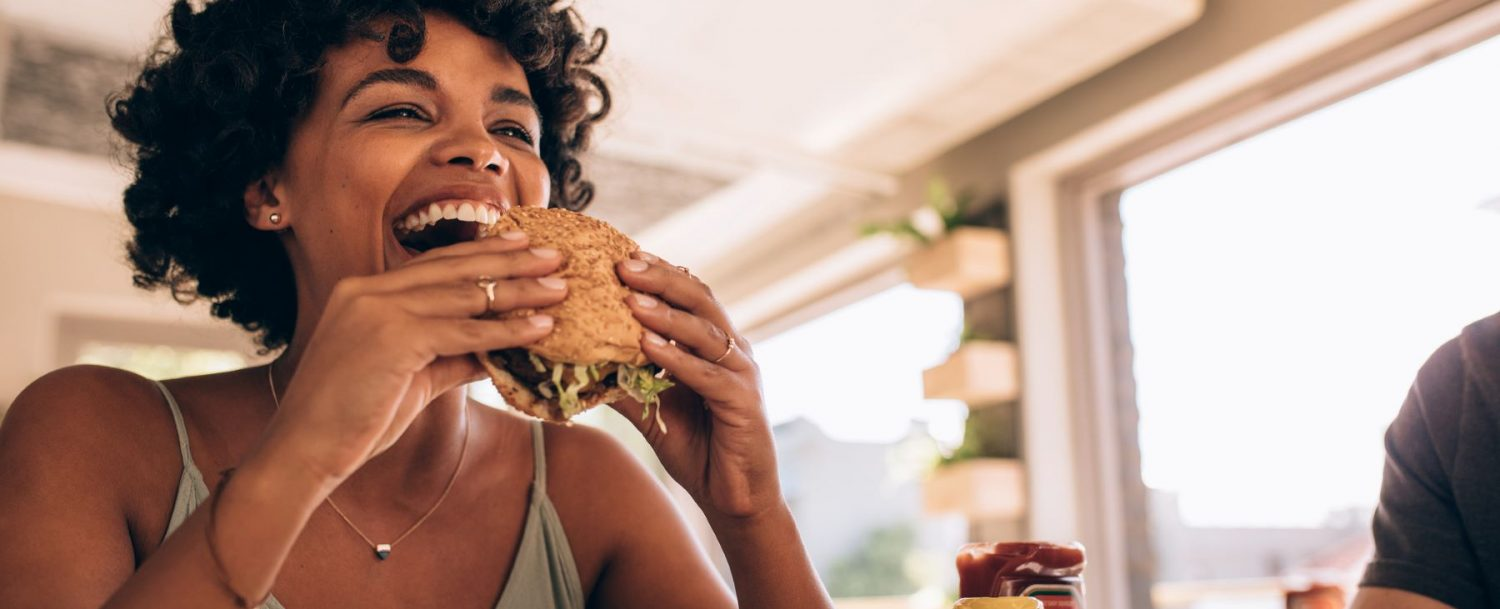 Woman eating a burger at a restaurant.